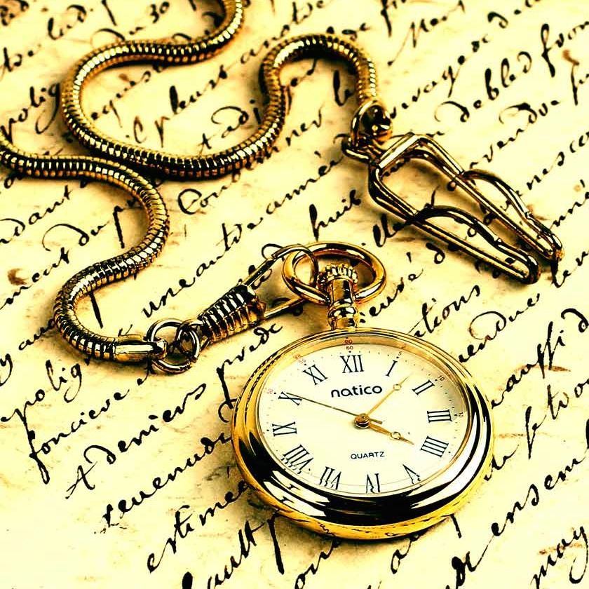 a gold pocketwatch atop a page of old-fashioned writing